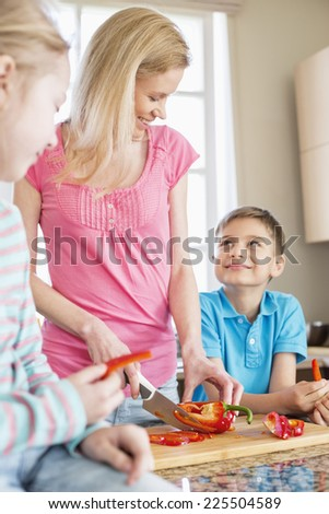 Happy woman chopping red bell pepper while standing with children in kitchen - stock photo
