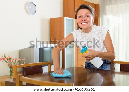 Happy woman cleaning furniture with snippet and spray  - stock photo