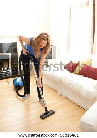 Happy woman cleaning her living room with a vacuum cleaner - stock photo