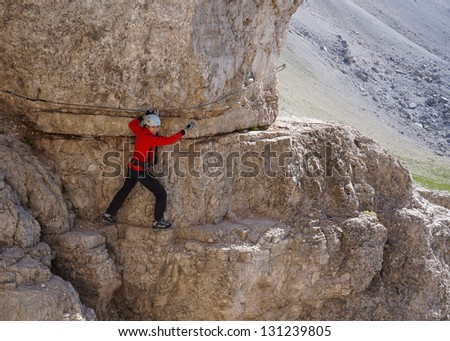Happy woman climbing on a via ferrata trail - stock photo