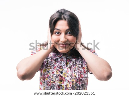 Happy woman closed her ears with hands and looking at camera isolated on a white background - stock photo