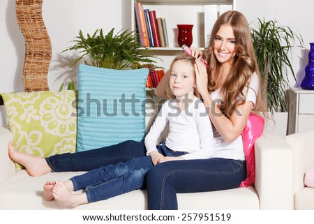 Happy woman combing child's hair - stock photo