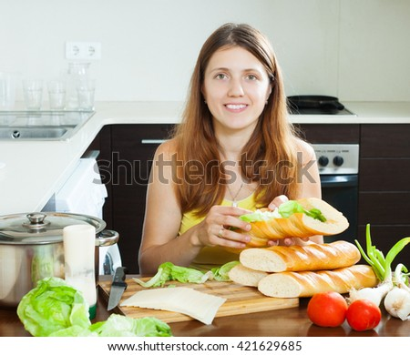 Happy woman cooking sandwiches with cheese and vegetables in  kitchen