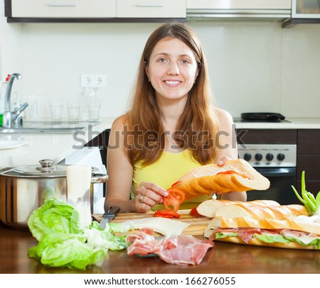 Happy woman cooking sandwiches with tomato and  hamon in her kitchen
