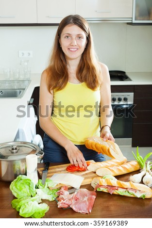 Happy woman cooking spanish sandwiches (bocadillo) with tomato and  hamon in  kitchen