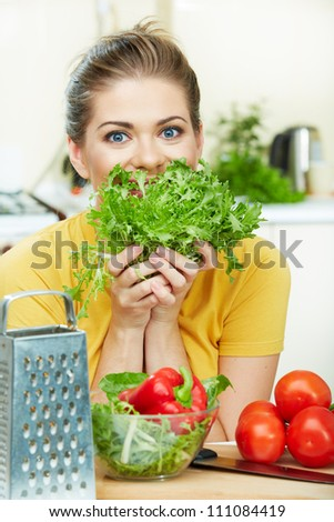 Happy woman cooking vegetables green salad in the kitchen