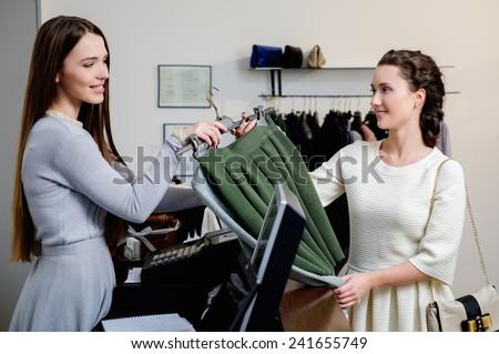 Happy woman customer paying in fashion showroom - stock photo