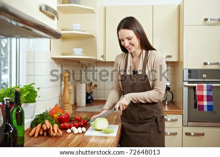 Happy woman cutting kohlrabi (Brassica oleracea var. gongylodes L.) in the kitchen - stock photo