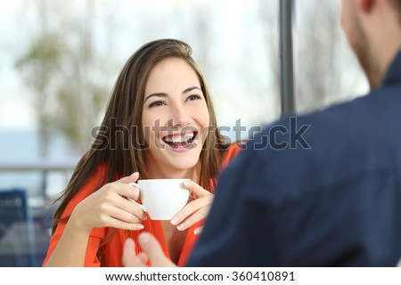 Happy woman dating in a coffee shop looking at her partner and holding a cup - stock photo