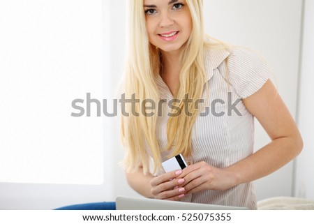 Happy woman doing online shopping at home . Close- up of a hand holding a credit card next to a laptop