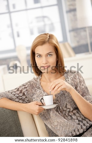 Happy woman drinking coffee at home, holding saucer, stirring coffee, smiling at camera.?