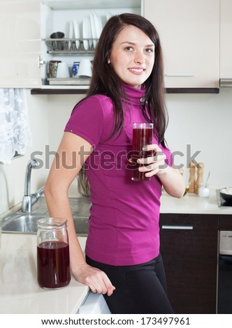 Happy woman drinking fresh fruit-drink from glass