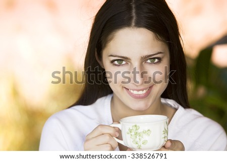 Happy woman drinking tea outdoors