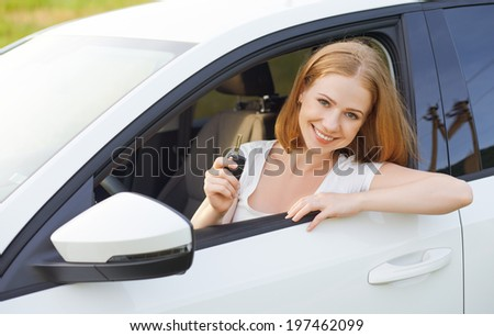 happy woman driver with keys driving a new car - stock photo