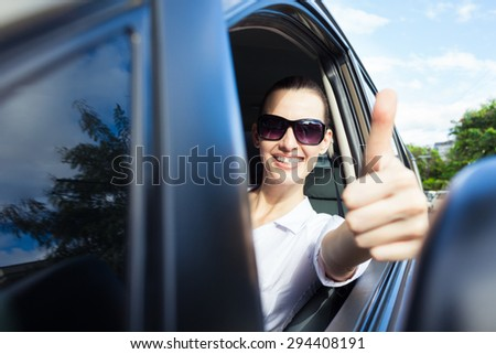 Happy woman driver with thumbs up. - stock photo
