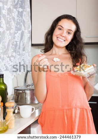 Happy woman eat chocolate dessert and smiling in home  kitchen