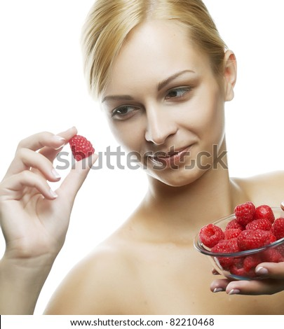 happy woman eating a raspberry. Isolated over white - stock photo