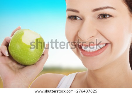 Happy woman eating an apple. - stock photo