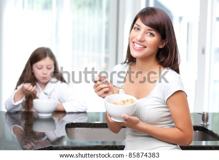 Happy woman eating breakfast cereal with daughter - stock photo