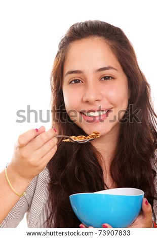 Happy woman eating cereal on a blue plate