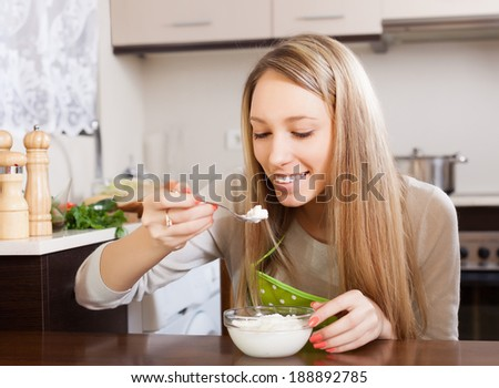 Happy woman eating cottage cheese at table  - stock photo