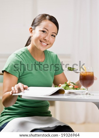 Happy woman eating healthy lunch while reading magazine - stock photo