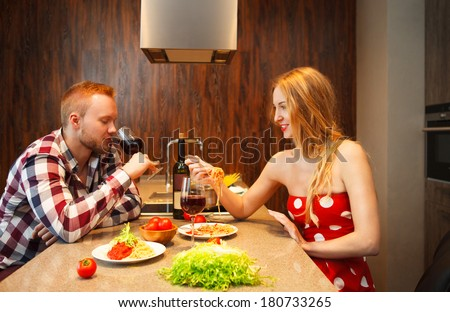 Happy woman eating pasts while man tasting red wine in a kitchen. Couple on the date - stock photo