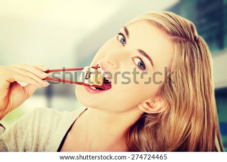 Happy woman eating tasty sushi
