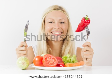 Happy woman eating vegetable for meal. - stock photo