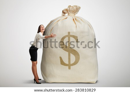 happy woman embracing big bag with money and smiling over light grey background - stock photo