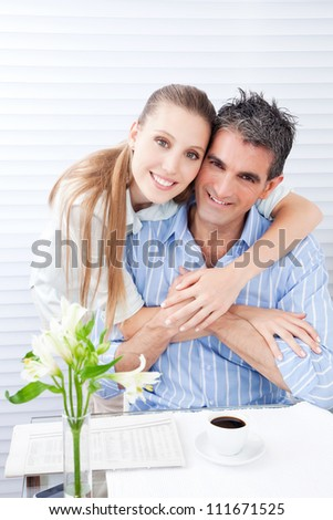 Happy woman embracing her husband at breakfast .