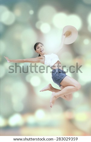 Happy woman enjoy holiday and jumps with bokeh background while holding hat - stock photo