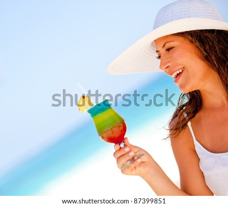 Happy woman enjoying a tropical cocktail at the beach - stock photo