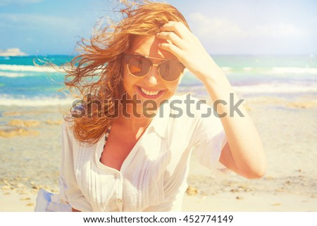 Happy woman enjoying at the beach. Summer vacations concept