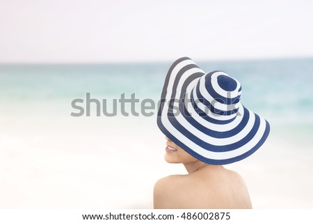Happy woman enjoying beach relaxing joyful in summer by tropical blue water.  model happy on travel wearing beach sun hat, Big Island,