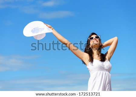 Happy woman enjoying freedom on summer.  Blissful girl raising arms to the sky. - stock photo