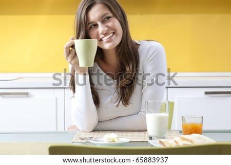 Happy woman enjoying her healthy breakfast - stock photo
