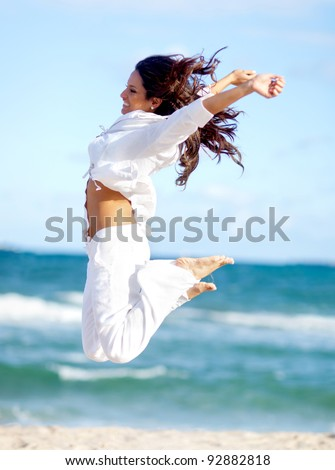 Happy woman enjoying her time at the beach and jumping - stock photo