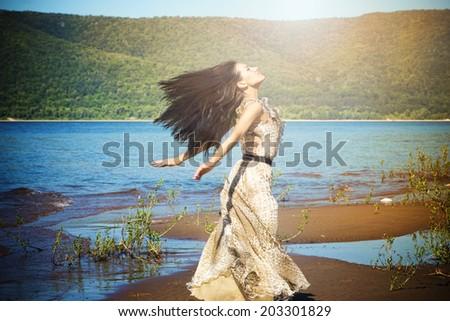 Happy woman enjoying nature. Beautiful girl on the beach in summer. Freedom concept. Sunbeams. Enjoyment. - stock photo