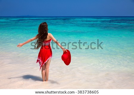 Happy woman enjoying on exotic beach in summer by tropical blue water. Attractive girl in red dress resting, outdoor portrait. Bliss freedom concept. Travel. - stock photo