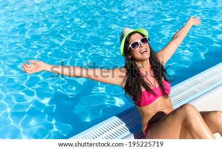 Happy woman enjoying summer vacation at swimming pool. Funky brunette girl on her summertime holidays. - stock photo