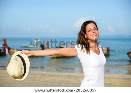 Happy woman enjoying travel vacation to Krabi, Thailand. Joyful brunette having fun and smiling on Railay Beach. - stock photo