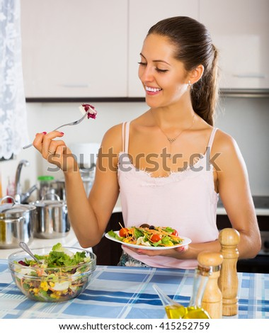 Happy woman enjoying vegetable salad and smiling