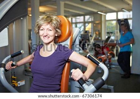 Happy woman exercising on rowing machine in gym - stock photo