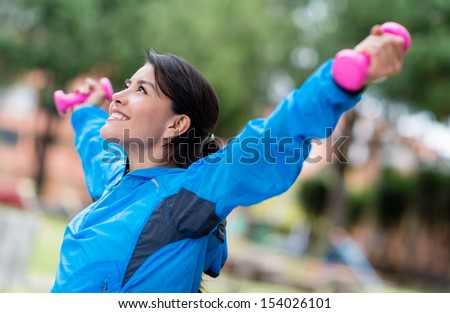 Happy woman exercising with arms up and free-weights  - stock photo