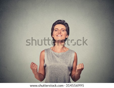 happy woman exults pumping fists ecstatic celebrates success - stock photo