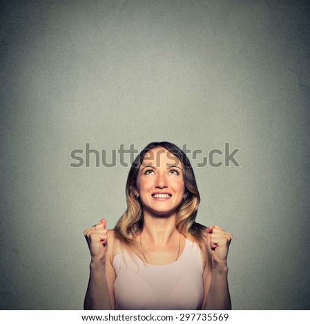 happy woman exults pumping fists ecstatic celebrates success looking up isolated on gray wall background with copy space  - stock photo