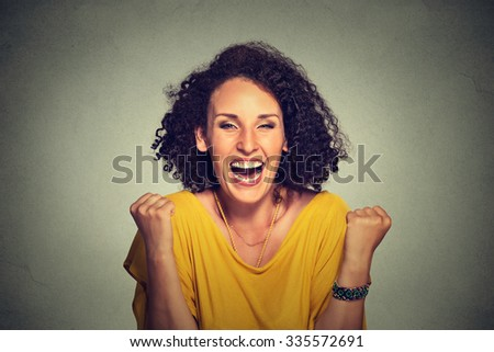 happy woman exults pumping fists ecstatic celebrates success on gray background  - stock photo