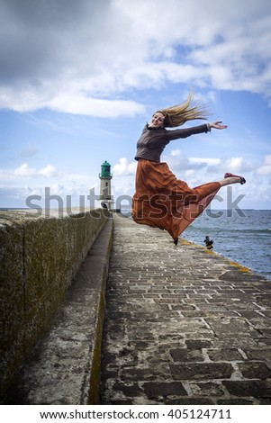 Happy Woman fool of energy Jumping near the ocean in the sky; on the long pier with lighthouse - stock photo