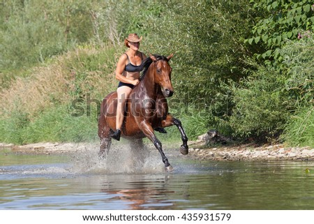 Happy woman galloping in the water - stock photo